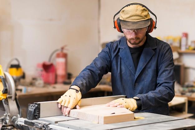 ワークショップで木製ブロックを調整する男性の大工の肖像