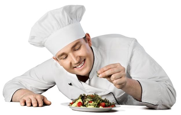 흰색 배경에 격리된 샐러드를 준비하는 남성 요리사 요리사의 초상화