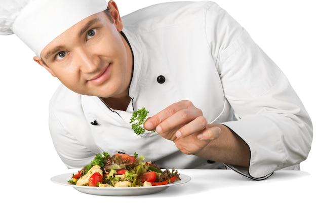白い背景で隔離のサラダを準備する男性シェフ料理人の肖像画