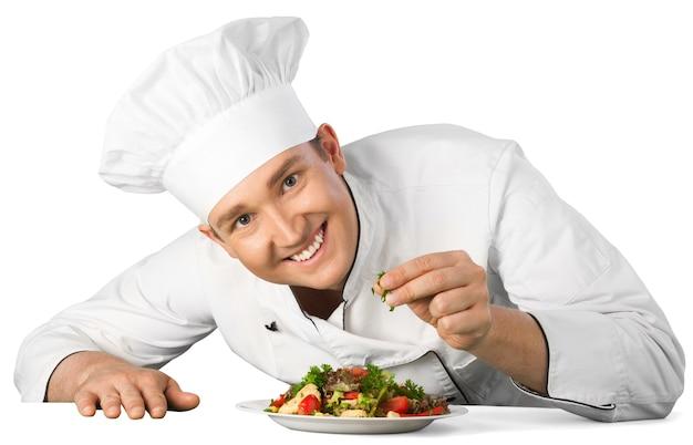 배경에 고립 된 샐러드를 준비하는 남성 요리사 요리사의 초상화