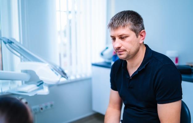 男性歯科医の肖像画が患者に相談します。職場の専門医。