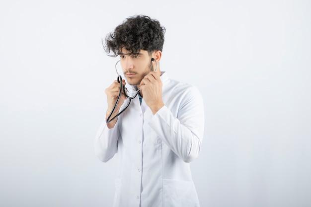 청진기를 들고 듣고 있는 남성 의사의 초상화.