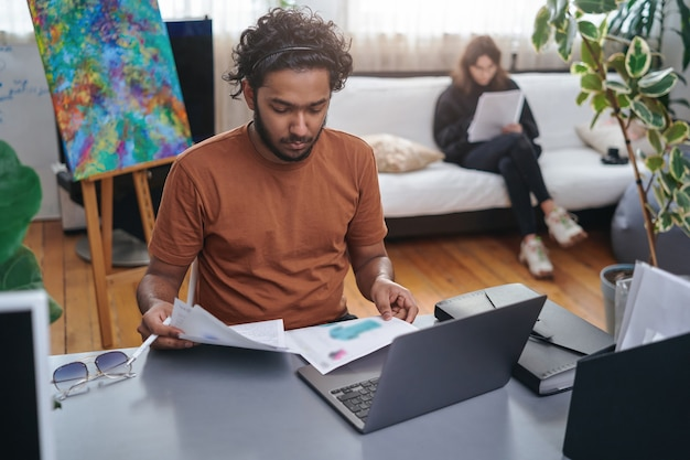 Портрет мужчины индийского дизайнера и стилиста, он делает свою работу, сидя за столом на фоне своего коллеги, она сидит на диване.