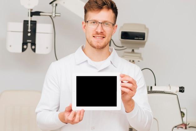 Портрет мужчины окулист, представляя шаблон планшета
