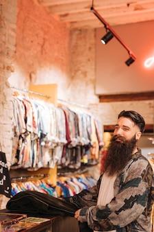 Портрет мужского владельца за прилавком в магазине одежды