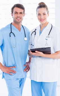 Portrait of a male surgeon and female doctor with medical reports at the hospital