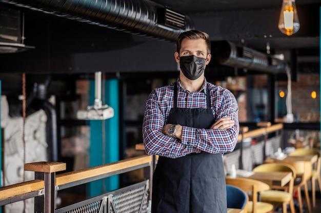 腕を組んでモダンな屋内レストランに立っている男性ウェイターの肖像画