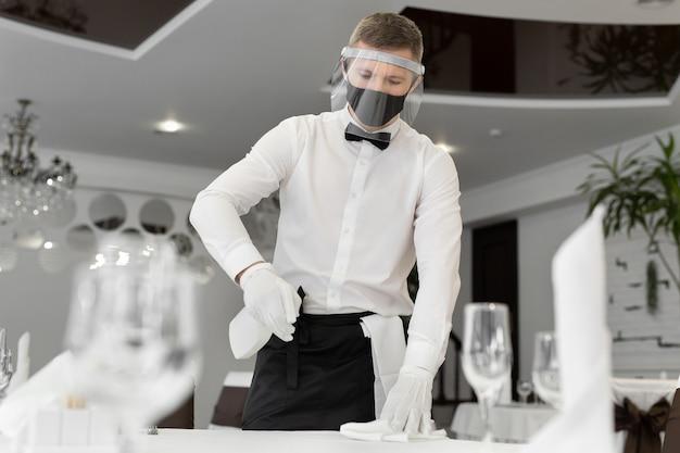 社会的な距離の間にカフェでテーブルを掃除しているフェイスマスクとフェイスシールドを身に着けている男性ウェイターの肖像画