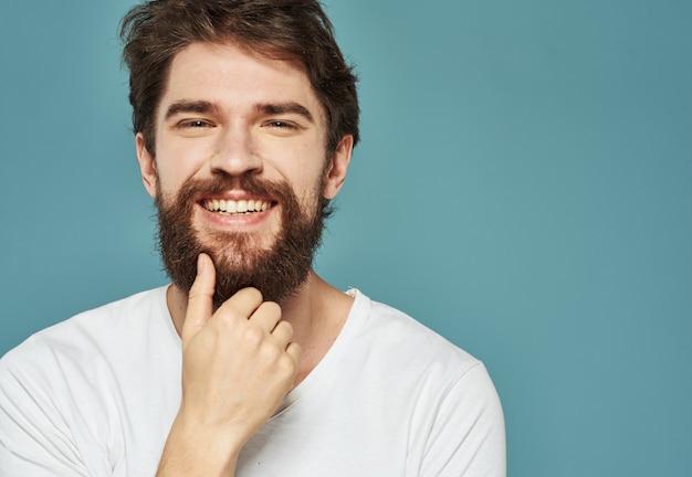 남자 파란색 벽 근접 자른보기 흰색 t- 셔츠 잘 생긴 미소의 초상화.