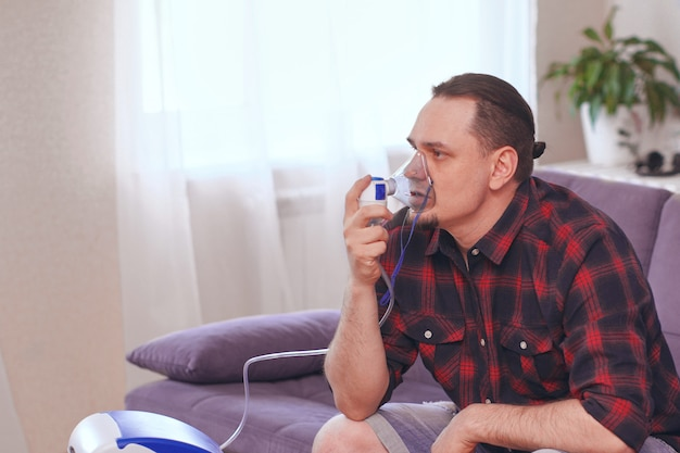 Портрет мужчины, дыхание через ингалятор маску в домашних условиях. лечение заболеваний легких. копировать пространство