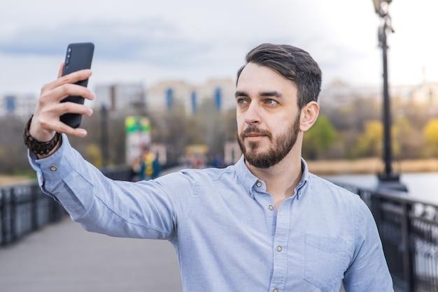 Портрет мужчины-бизнесмена с бородой в рубашке, который делает селфи на смартфоне