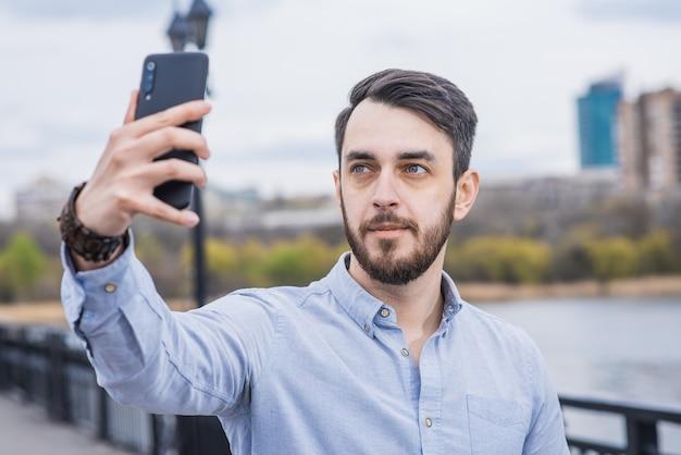 Портрет мужчины-бизнесмена с бородой в рубашке, который делает селфи на смартфоне Premium Фотографии