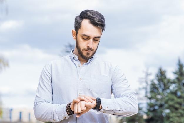 Портрет мужчины-бизнесмена с бородой, смотрящего на часы на его запястье