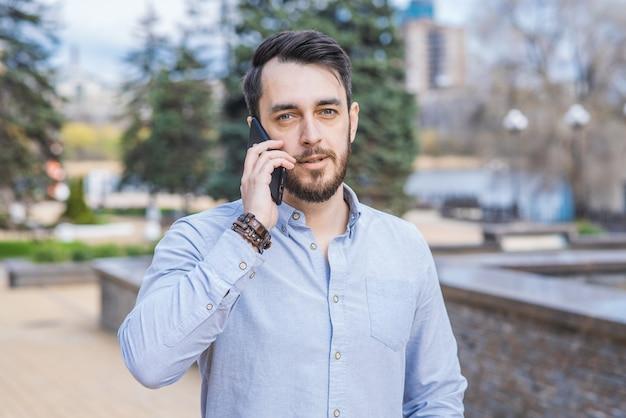 Портрет мужчины-бизнесмена с бородой, который разговаривает по телефону на улице