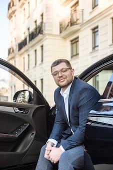 街のシーンで車を持っている男性実業家の肖像画