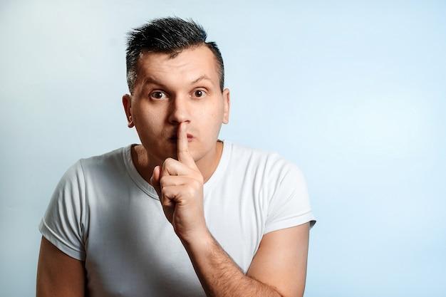 Портрет мужчины крупным планом. показывает жест рукой спокойно, не шуметь, пальцем жести к губам.