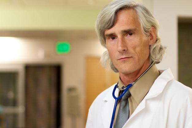 Портрет мужчины-врача со стетоскопом под огнями