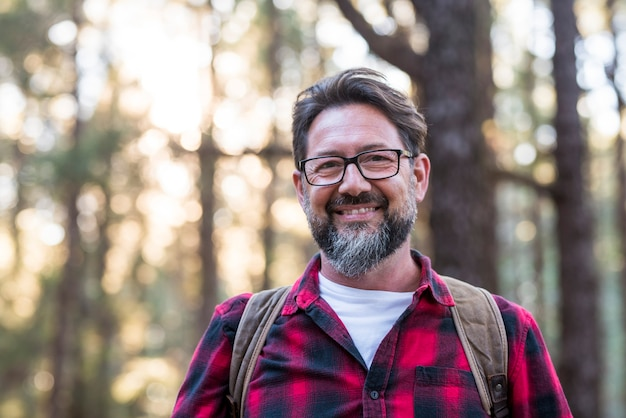 森の中のトレイルを歩いている男のハイカーの肖像画。森の背景にバックパックと幸せなライフスタイル旅行男性-環境と自然の屋外の人々を楽しんでいます