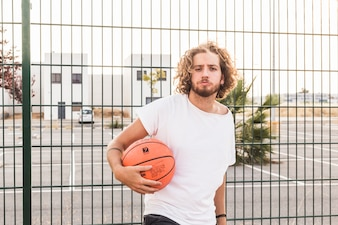 Portrait of a man holding basketball standing against fence