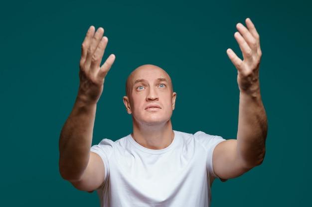 Портрет мужчины, подняв руки и глядя вверх