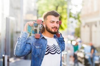 Portrait of a man holding skateboard on his shoulder