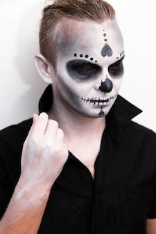 할로윈 해골 밝은 배경에 검은 색 티셔츠를 입은 남자의 초상화는 자신의 감정을 보여주기 위해 구성합니다. 할로윈 파티 또는 공포 테마. 멕시코 문화.
