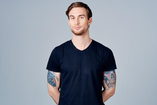 彼の腕のブロンドの髪の灰色の背景に入れ墨と青いtシャツを着た男の肖像画。高品質の写真