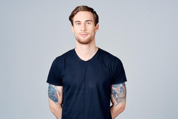 彼の腕のブロンドの髪の灰色の背景に入れ墨と青いtシャツの男の肖像画
