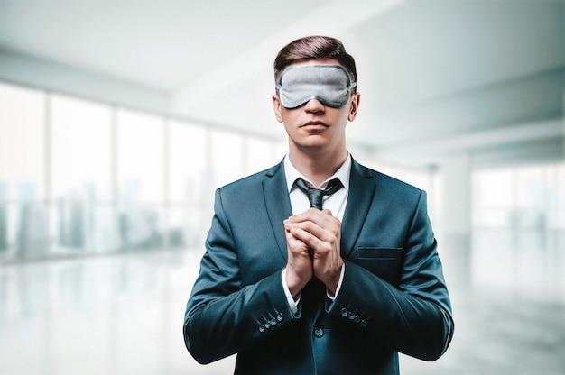 Портрет мужчины в деловом костюме. он молится, стоя в офисе. на глазах у него маска для сна. слепая бизнес-концепция.