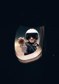 Портрет мужчины в шлеме. он смотрит в иллюминатор самолета и показывает фигуру в форме сердца. концепция путешествий и страхования.