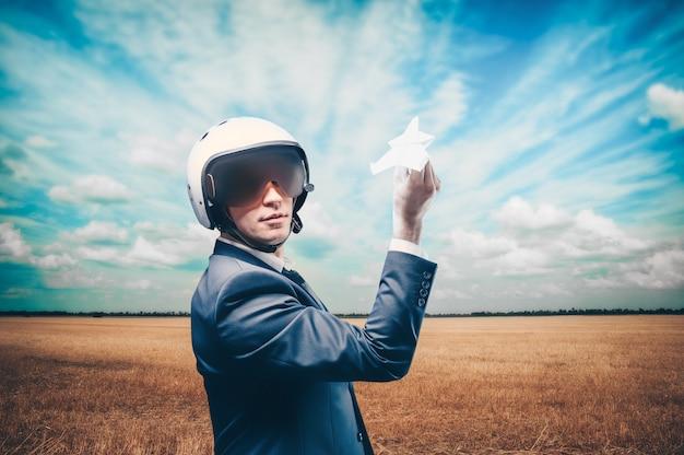 パイロットのヘルメットをかぶった男の肖像画。彼は野原に立ち、紙飛行機を打ち上げます。ビジネスコンセプト。ミクストメディア