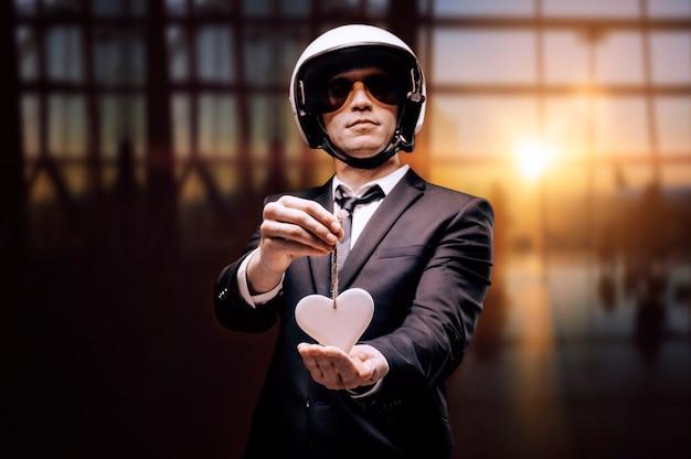 Портрет мужчины в шлеме, стоящего в аэропорту с белым сердцем в руках. концепция путешествий и страхования.
