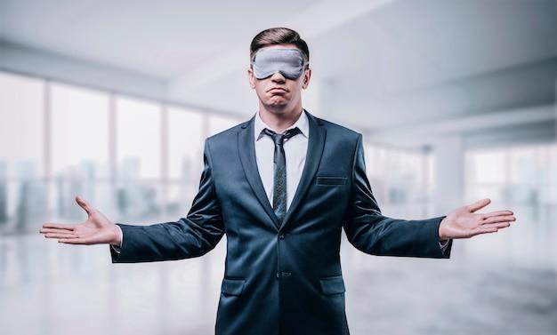 Портрет мужчины в маске для сна. он стоит в недостроенном небоскребе. слепая бизнес-концепция. строительство.