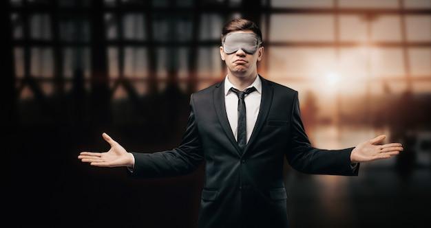 수면 마스크에 남자의 초상화. 그는 공항 터미널에 서서 불신앙에 손을 뻗는다.
