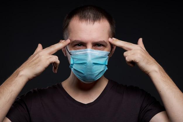 暗い背景、コロナウイルス感染症の医療マスクの男の肖像画 Premium写真