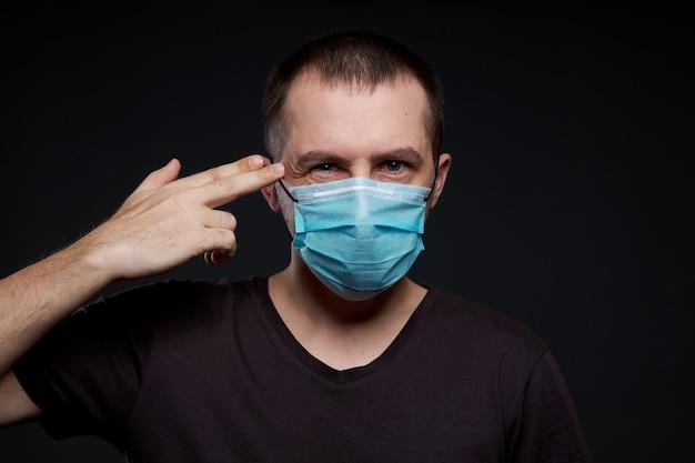 暗い壁、コロナウイルス感染症の医療マスクの男の肖像