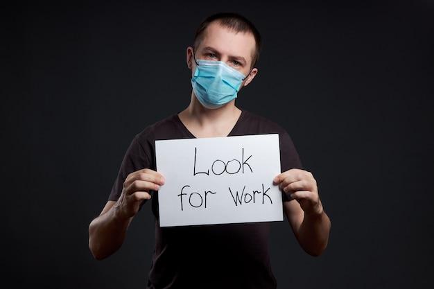暗い背景、コロナウイルス感染症の仕事を探している兆候と医療マスクの男の肖像画