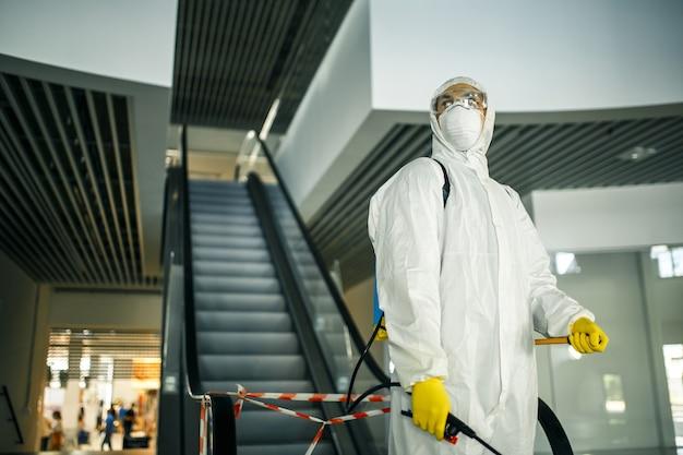 Портрет мужчины в дезинфицирующем костюме для дезинфекции, держащего спрей возле эскалатора в пустом торговом центре. волонтер убирает общественные места для предотвращения заражения covid-19. концепция осведомленности о здоровье.