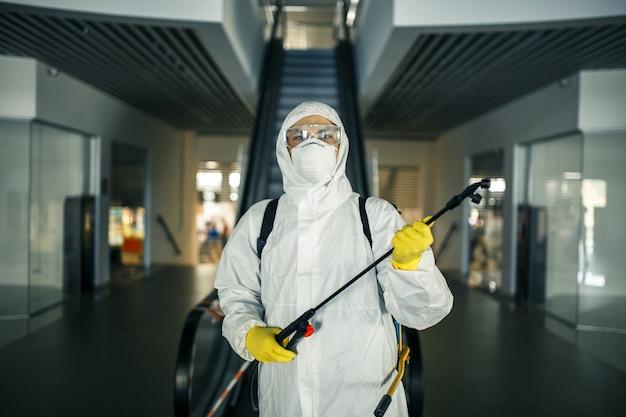 空のショッピングモールのエスカレーターの近くにスプレーを保持している消毒消毒スーツの男の肖像画。 covid-19を防ぐために公共の場所を掃除するボランティア。健康意識の概念。