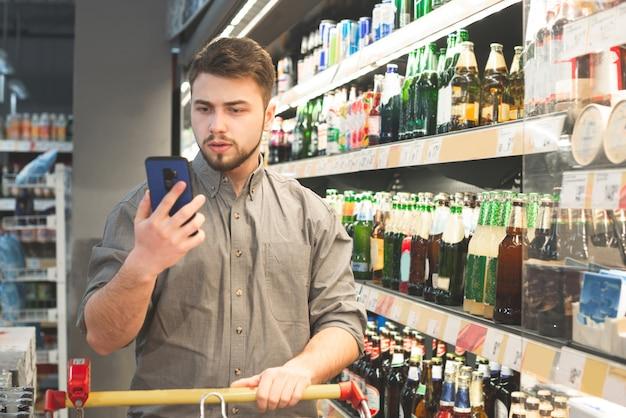 シャツを着た男性の肖像画がスーパーのアルコール部門にあり、ビールの棚の近くでスマートフォンを使用しています