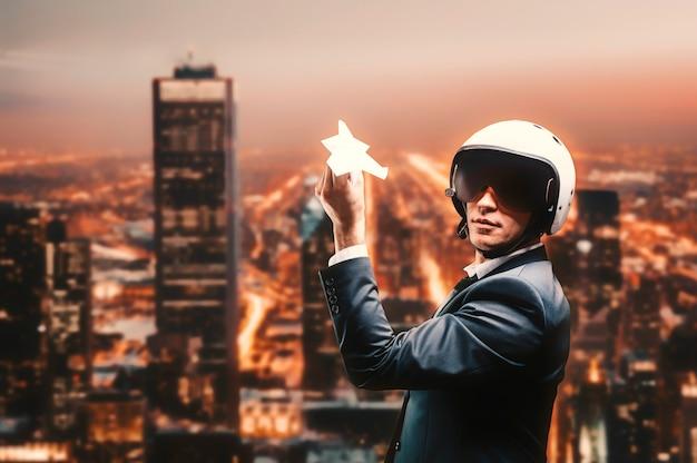 Портрет мужчины в костюме и шлеме. он запускает бумажный самолетик с крыши небоскреба. бизнес-концепция. смешанная техника