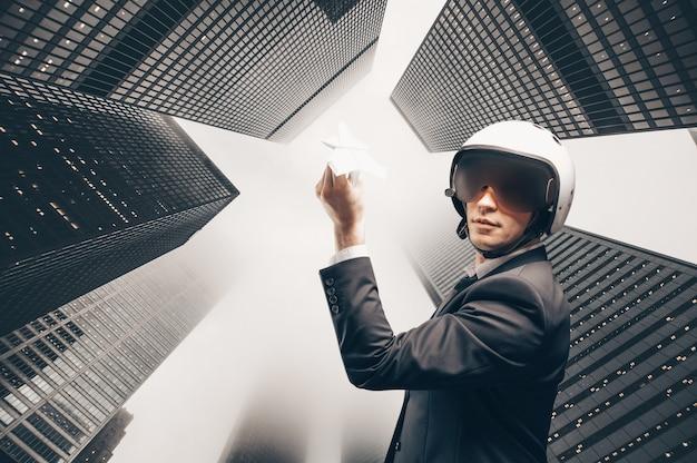 Портрет мужчины в костюме и шлеме. он запускает бумажный самолетик на крыши небоскребов финансового квартала. бизнес-концепция. смешанная техника