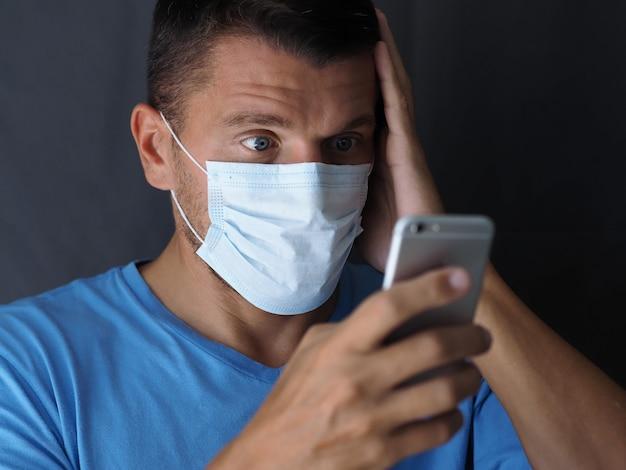 自宅で彼の携帯電話でニュースを見ている外科用医療マスクの男の肖像。人間の感情、顔の表情、驚いて驚いた男、口を開いた、目。 covid-19コンセプト
