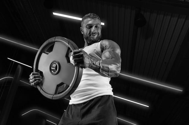 Портрет мужчины в белой футболке, тренирующегося в тренажерном зале с дисками со штангой. прокачка бицепса. концепция фитнеса и бодибилдинга.
