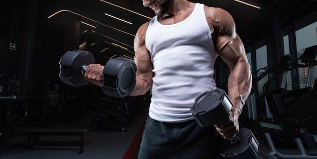 Портрет мужчины в белой футболке, тренирующегося в тренажерном зале с гантелями. прокачка бицепса. концепция фитнеса и бодибилдинга. смешанная техника
