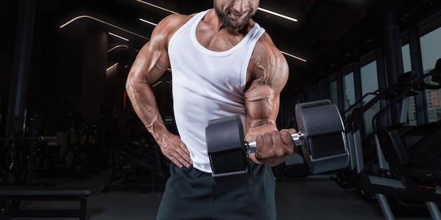 Портрет мужчины в белой футболке, тренирующегося в тренажерном зале с гантелями. прокачка бицепса. концепция фитнеса и бодибилдинга.