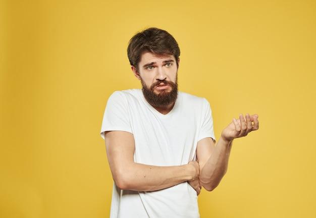 흰색 tshirt에서 남자의 초상화 자른보기 노란색 배경 의아해 보이는 모델