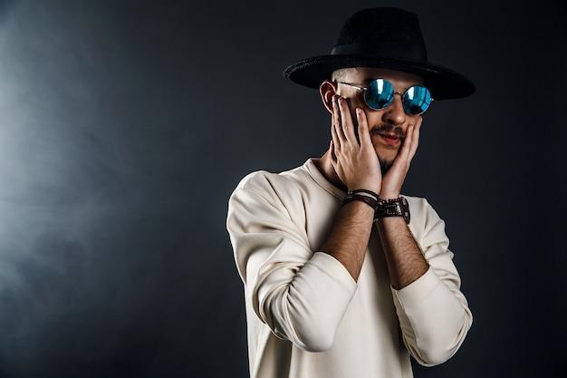 챙이 넓은 모자를 쓰고 어두운 배경에서 카메라를 바라보는 선글라스를 쓴 남자의 초상화