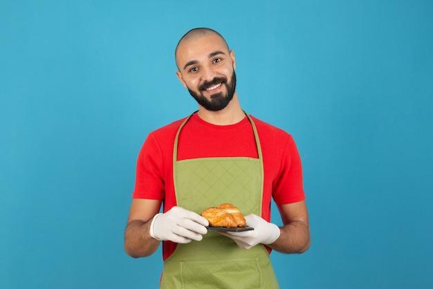 Портрет мужчины в фартуке и перчатках, держа свежую выпечку.