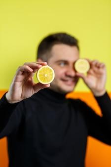 Портрет мужчины в черном реглане с разрезанным лимоном вместо глаз. парень с лимонами возле лица. улыбка на его лице